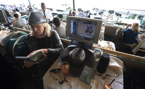 "Carol ""Lucky Lady"" Stogsdil peruses the racing form in search of a winner."